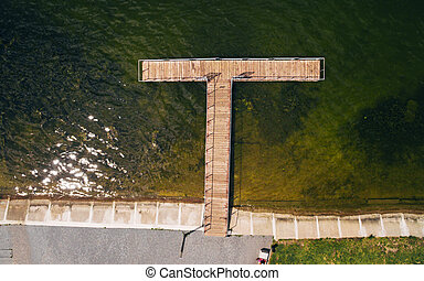 Aerial view of the wooden pier on the lake on a sunny day.