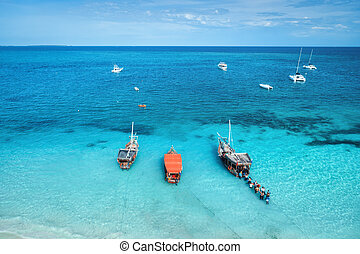 Aerial view of the yachts, fishing boats in transparent sea