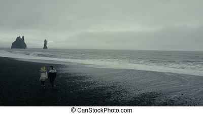 Aerial view of the young couple walking on the black volcanic beach near the troll toes cliffs in Iceland.