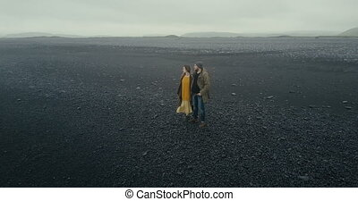 Aerial view of the young hipster couple walking on black volcanic beach in Iceland. Man and woman enjoying the nature.