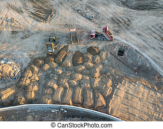 Aerial view of three multi-colored dump tip trucks unloading in a designated place at a construction site, soil poured out from a quarry poured out of a quarry, around a large number of sand mounds