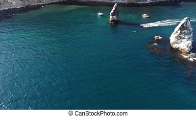 Aerial view of tourist boats in the sea bay next to individual rocks and high rocky coast. Luxury Mediterranean holidays.