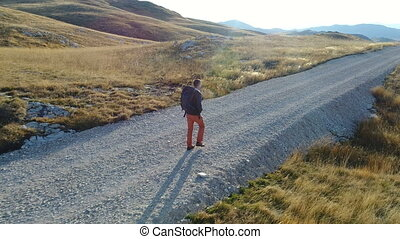 tourist with a backpack is walking along a gravel road -...