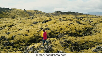 Aerial view of tourists woman standing on the rock on lava...