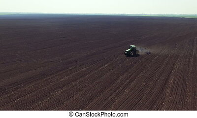 Aerial view of tractor plowing fertile soil in spring day,...