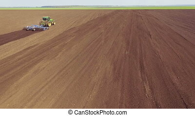 Aerial view of tractor plowing the fields, movement for tractor