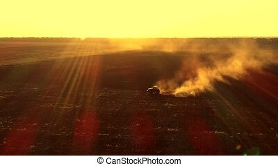 Aerial view of tractor plowing the ground with huge dust...