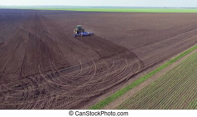 Aerial view of tractor plowing the soil on a fertile field