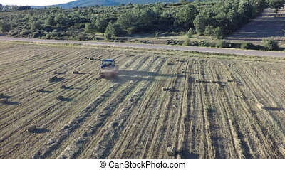 Aerial view of tractor preparing square bales at dusk, 4k -...