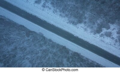 Aerial view of traffic on the road passing through the winter forest in blizzard