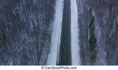 Aerial view of traffic on the road passing through the winter forest in winter