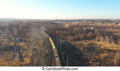 Aerial view of train moving along railway and shipping industrial goods. Drone following for locomotive with freight wagons passing countryside. Cargo transportation or delivery concept. Top view.