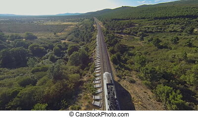 Aerial view of train running in the country, heading forward...