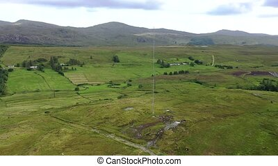 Aerial view of transmitter tower on an agricultural field in the Irish highlands by Glenties in County Donegal.