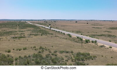 Straight road, following truck, clear day, blue sky, aerial view