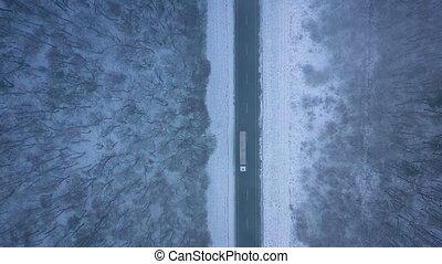 Aerial view of trucks on the road passing through the winter forest in blizzard