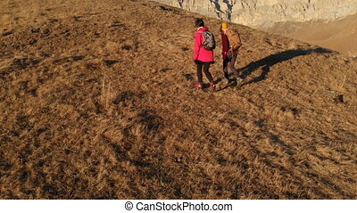 Aerial view of two girls traveler with backpacks and cameras...