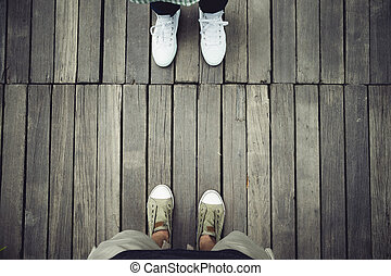 aerial view of two people standing opposite on old wood...