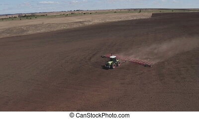 Aerial view of Two tractors going in opposite direction and...
