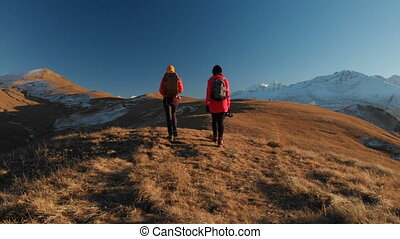 Aerial view of two traveling girls with backpacks and...