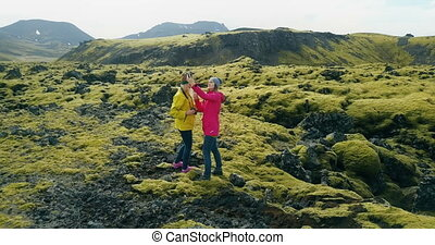 Aerial view of two woman on lava field in Iceland. Copter...