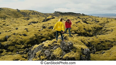 Aerial view of two woman standing on the rock, hiking together. Copter flying around tourist in lava field in Iceland.