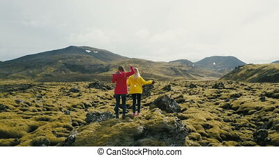 Aerial view of two woman standing on the rock in lava field in Iceland. Tourists looks on landscape, dancing and jumping