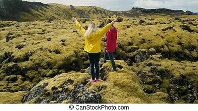Aerial view of two woman standing on the rock, looking on...