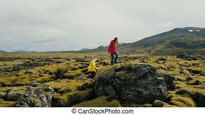 Aerial view of two woman walking on the lava field in...