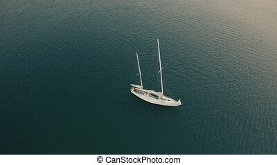 Aerial view of unknown man cruising on his sailboat with...