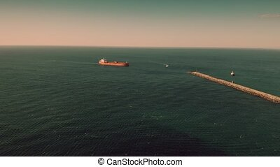 Aerial view of unknown red oil tanker moving at sea near...