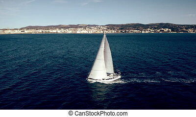 Aerial view of unknown sailboat cruising at sea - Aerial...