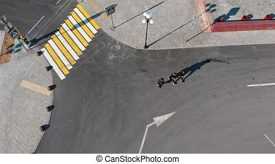 Aerial view of urban streets. Crosswalk. Three men walking...