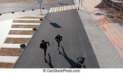 Aerial view of urban streets. Three men walking on the road....