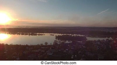 Aerial view of village and lake at sunset. 4K