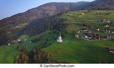 Aerial view of villas and church on Austrian mountains on green hills. Austrian village and an old Church on a hill. Summer time