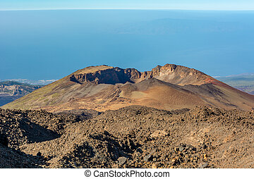 Aerial view of volcano cone raising above ocean