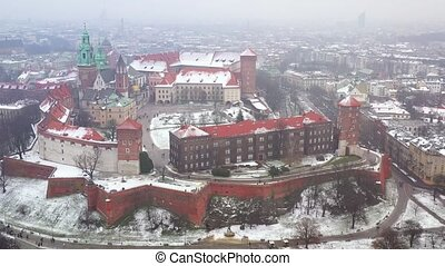 Aerial view of Wawel royal Castle and Cathedral, Vistula River, park, promenade and walking people in winter. Poland