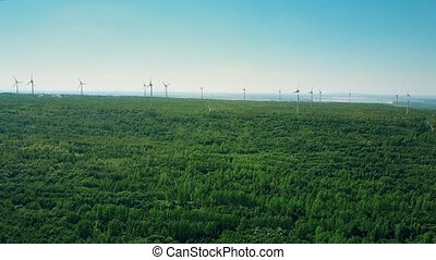 Aerial view of wind generators in forest area. Ecologic...