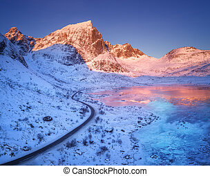 Aerial view of winding road, snow covered mountains and blue sky