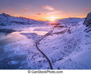 Aerial view of winding road, snow covered mountains at sunset