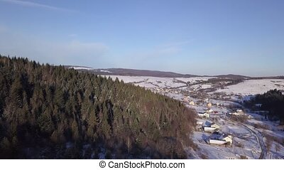 Aerial view of winter landscape with snowy hills and forest on the mountains
