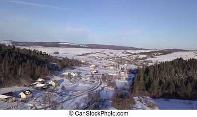 Aerial view of winter landscape with snowy hills, high trees and road underneath