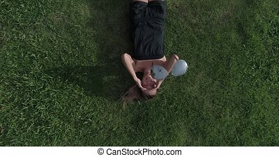 Aerial view of woman lying on the grass while drone is taking off the sunglasses from her face