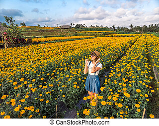 Aerial view of woman on a marigold field. Bali island.
