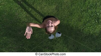 Aerial view of woman standing on the grass while drone is taking off the sunglasses from her face