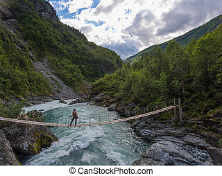 Aerial view of woman standing on the suspension bridge over a wild mountain river.