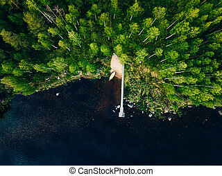 Aerial view of wooden pier with fishing boat on blue lake with green forest in Finland.
