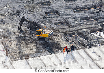 Aerial view of working excavator with builders standing near