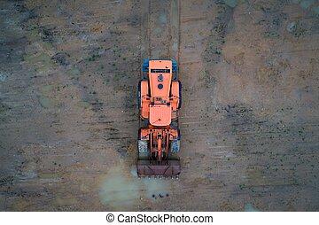 Aerial view of working orange loader bulldozer